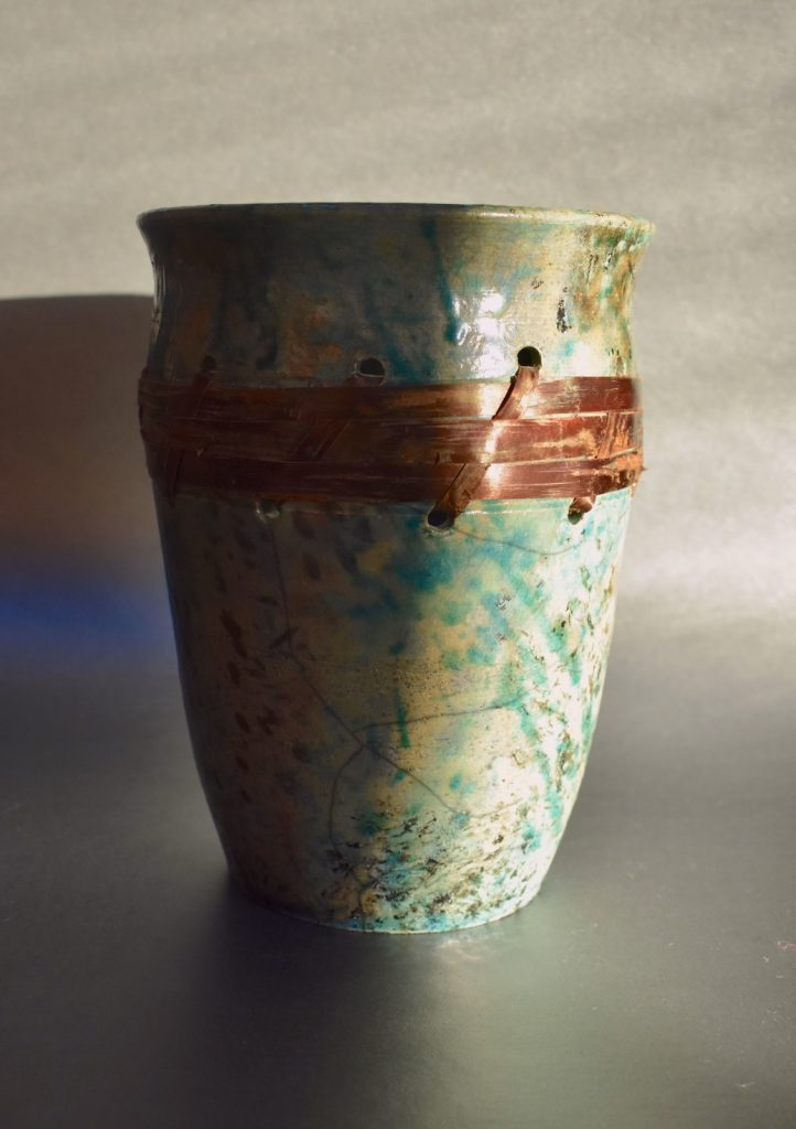 Teal and brown Raku pot with cherry bark weave by Ed Oldfield